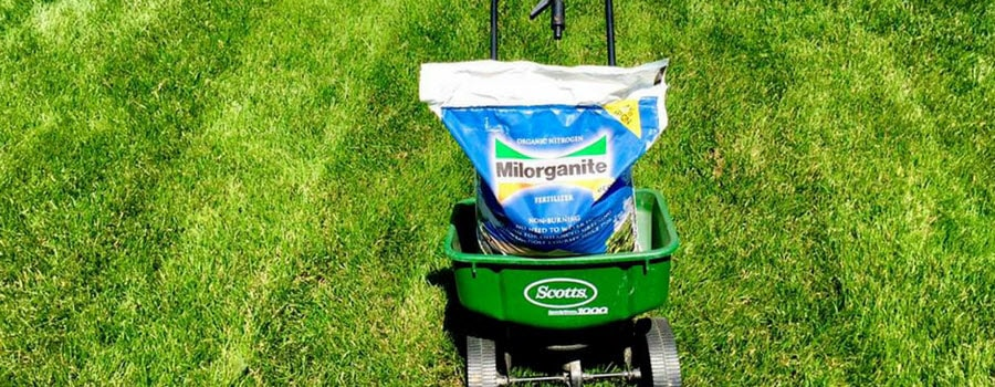 Bag of Milorganite in the lawn with a spreader