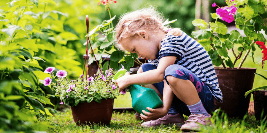 Outdoor Activites Kid in Garden watering a plant